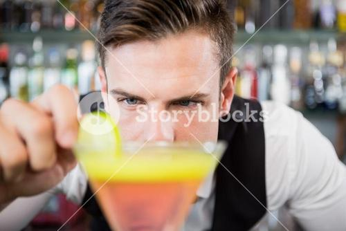 Waiter decorating cocktail with lime