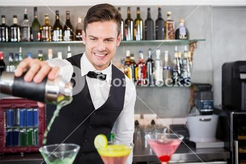 Waiter pouring cocktail into glasses