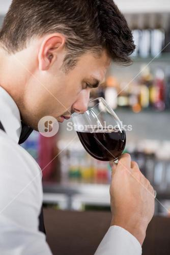 Waiter smelling a glass of wine