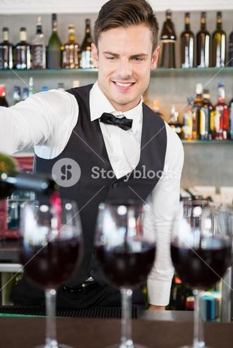 Waiter pouring wine into glasses