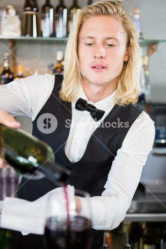 Waiter pouring wine into glass