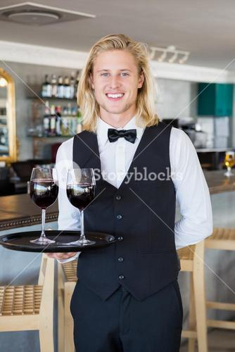 Portrait of waiter holding tray with glasses of red wine