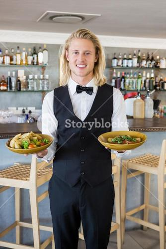 Waiter holding plated meals in restaurant