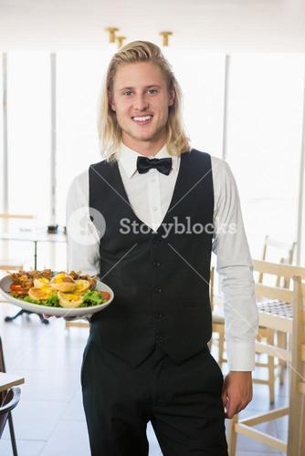 Waiter holding a plate of food in restaurant