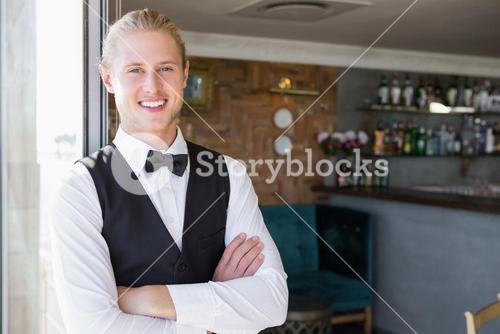 Waiter with arms crossed in restaurant