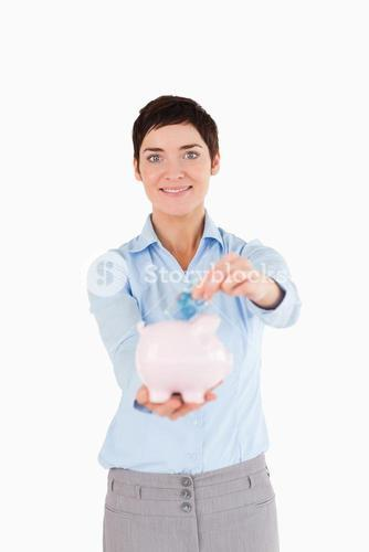 Businesswoman putting a bank note in a piggy bank
