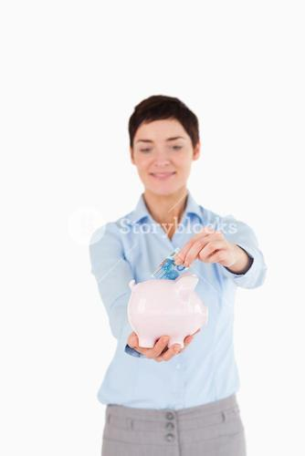 Bank worker putting a bank note in a piggy bank