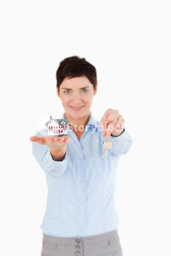 Woman showing keys and a miniature house