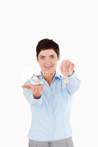Businesswoman showing keys and a miniature house