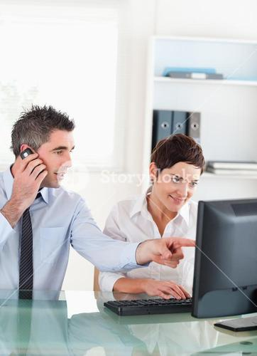 Portrait of a man showing something to his coworker on a computer