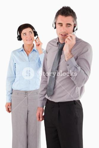 Portrait of coworkers speaking through headsets