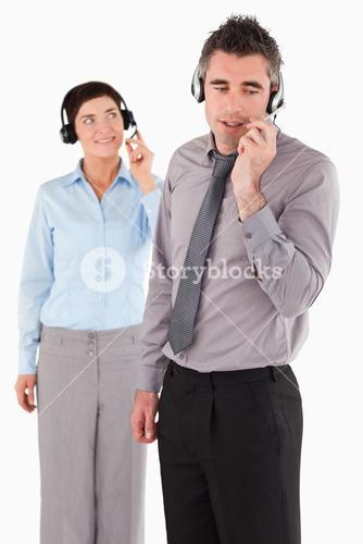Portrait of office workers speaking through headsets