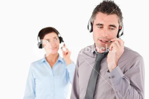 Office workers speaking through headsets