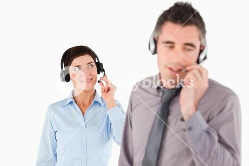 Business people speaking through headsets