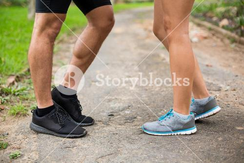 Couples feet standing on track