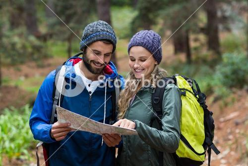 Happy hiker couple looking at map