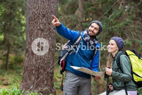 Hiker couple looking at map and pointing away