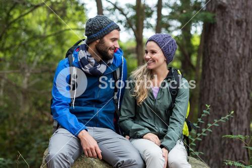 Hiker couple sitting together on rock