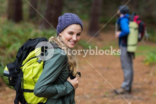Woman looking back while hiking in forest