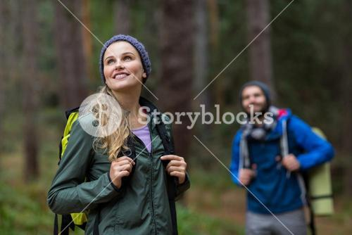 Beautiful woman looking at nature while hiking in forest