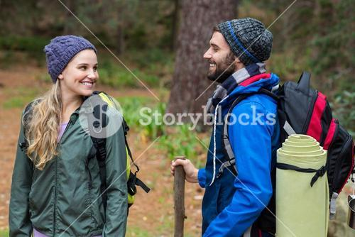 Hiker couple looking at each other in forest