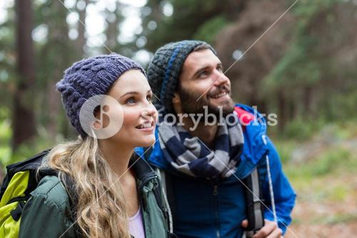 Hiker couple looking at nature in forest
