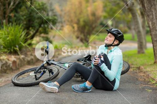 Female cyclist in pain holding her injured leg