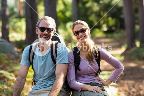 Portrait of hiker couple sitting on rock in forest