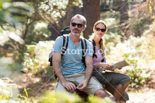 Hiker couple sitting on rock with map