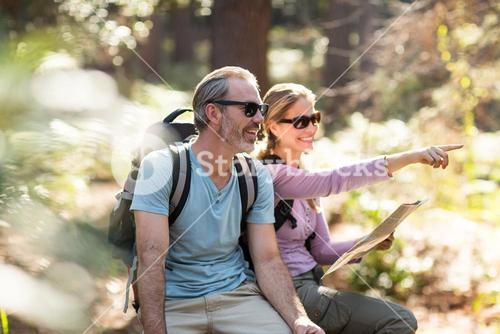 Hiker couple with map pointing in the distance