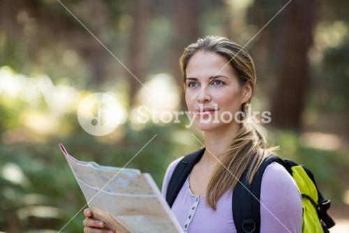 Confident woman standing with map