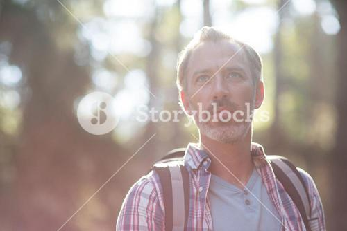 Hiker standing in forest carrying backpack