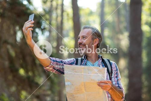 Happy hiker with map taking a selfie
