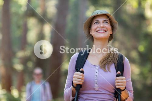 Smiling woman hiker hiking with trekking poles