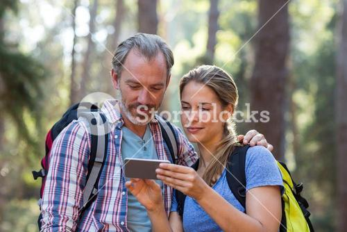 Hiker couple using mobile phone