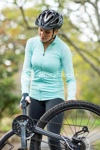 Fit woman repairing her bicycle