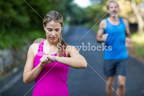 Fit woman checking time on wristwatch