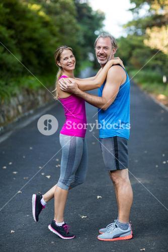 Smiling athletic couple embracing each other