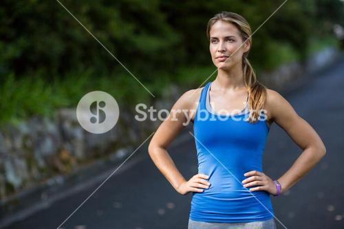 Thoughtful woman standing with hands on hip