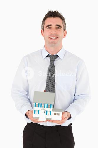 Businessman holding a miniature house