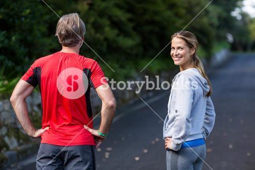Athletic couple standing with hands on hip on the road