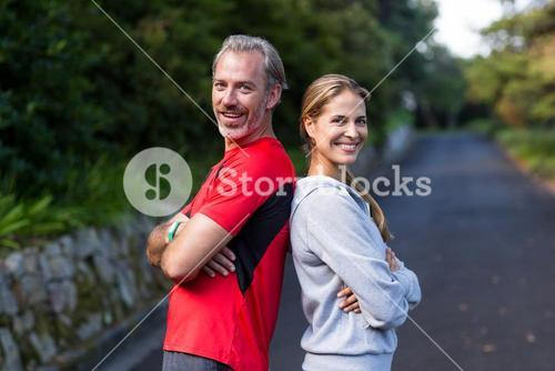 Athletic couple standing back to back on the open road