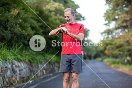 Athletic man checking time on wristwatch