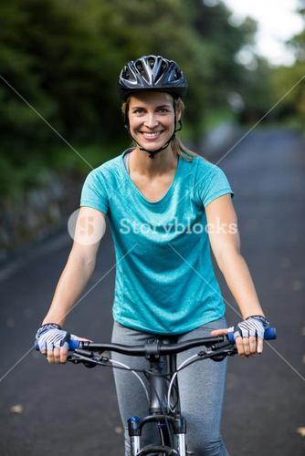 Smiling woman cycling on the road