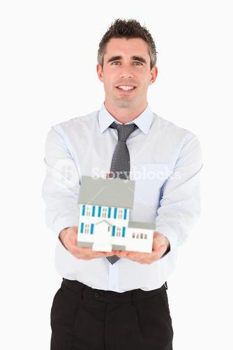 Real estate agent holding a miniature house