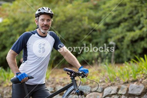 Man standing with mountain bike on the road