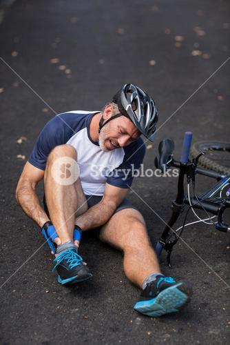 Male cyclist in pain holding her injured leg