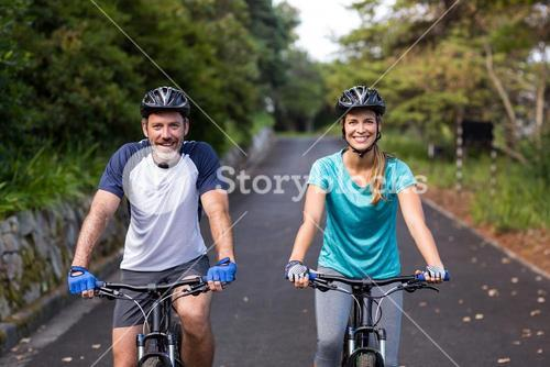 Athletic couple cycling on the open road
