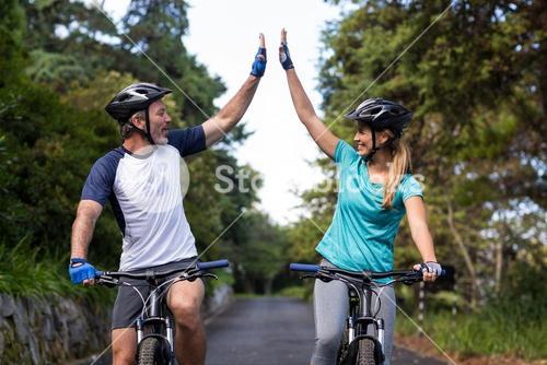 Athletic couple giving high five while riding bicycle on the road