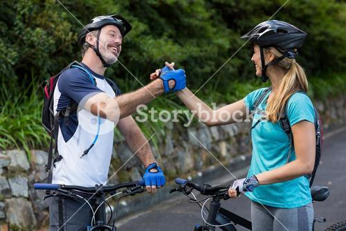 Athletic couple holding hands while riding bicycle